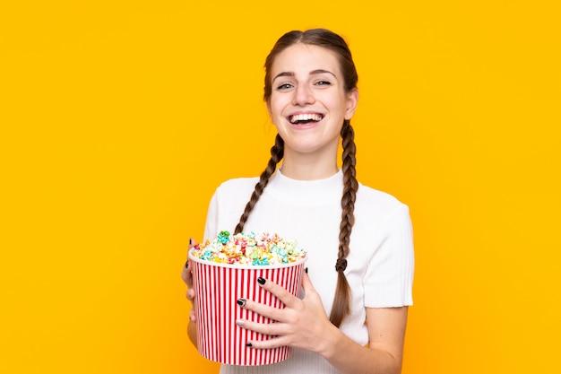 Mujer joven con palomitas de maíz sobre pared aislada