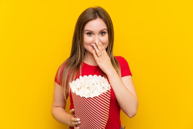 Mujer joven con palomitas de maíz sobre pared rosa con expresión facial sorpresa