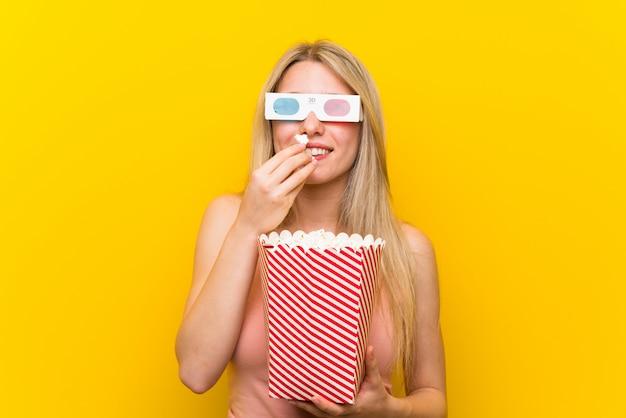 Mujer joven con palomitas de maíz sobre pared rosa