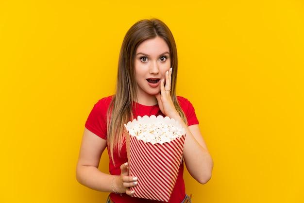 Mujer joven con palomitas de maíz sobre pared rosada con sorpresa y expresión facial en shock