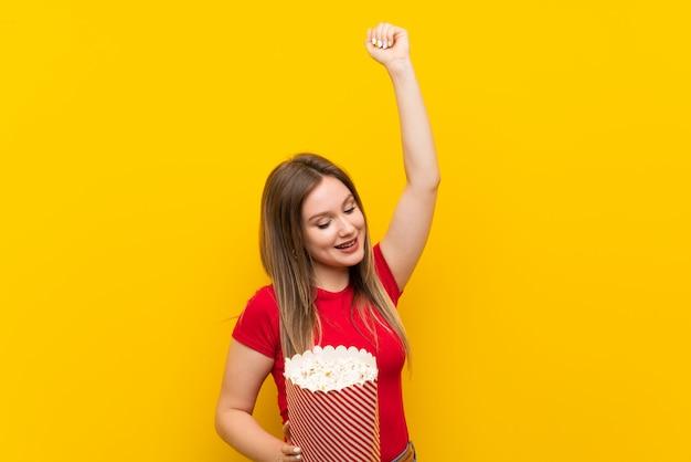 Mujer joven con palomitas sobre pared rosa celebrando una victoria