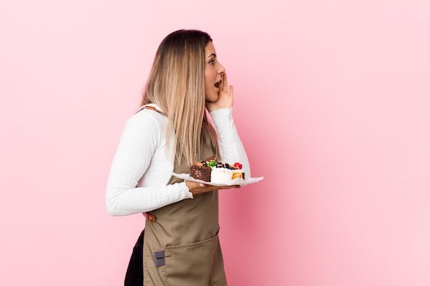 Mujer joven panadero con dulces gritando y sosteniendo la palma cerca de la boca abierta.
