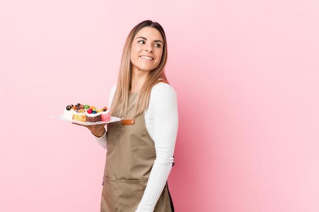 La mujer joven del panadero que sostiene los dulces mira a un lado sonriente, alegre y agradable.