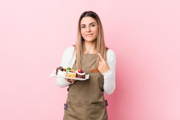 La mujer joven del panadero que sostiene los dulces que le señala con el dedo como si invitara se acerca.