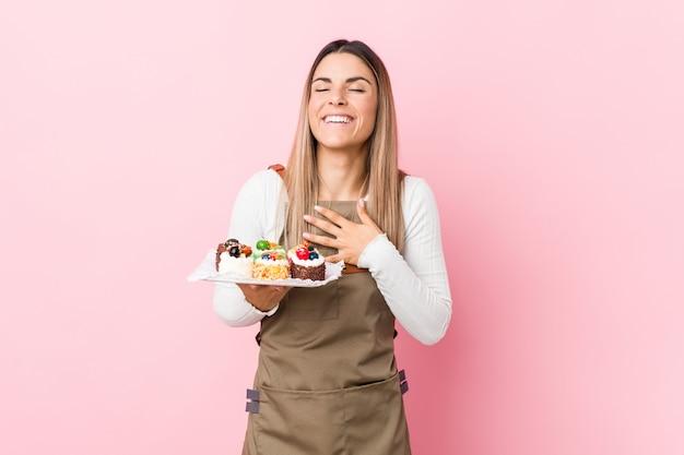 La mujer joven del panadero que sostiene los dulces ríe a carcajadas manteniendo la mano en el pecho.