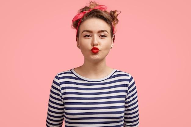 Mujer joven con pañuelo y camisa a rayas