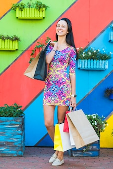 Mujer joven con paquetes cerca de pared
