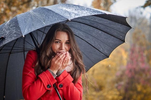 Mujer joven con paraguas en el parque otoño.