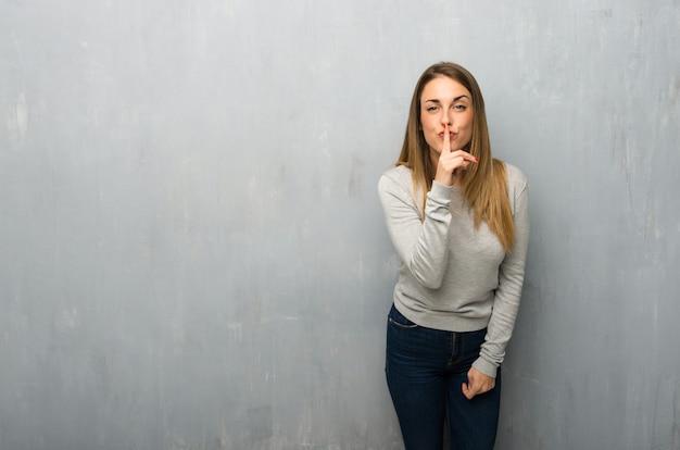 Mujer joven en la pared con textura que muestra un signo de silencio gesto poniendo el dedo en la boca