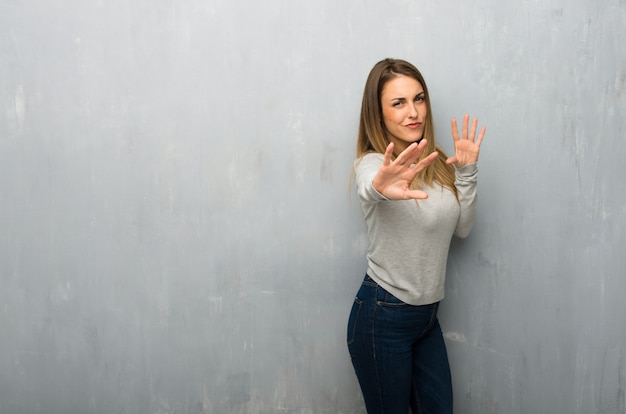 La mujer joven en la pared texturizada está un poco nerviosa y asustada estirando las manos hacia el frente