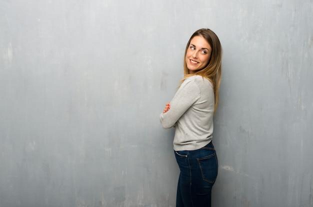 Mujer joven en la pared texturizada que mira sobre el hombro con una sonrisa