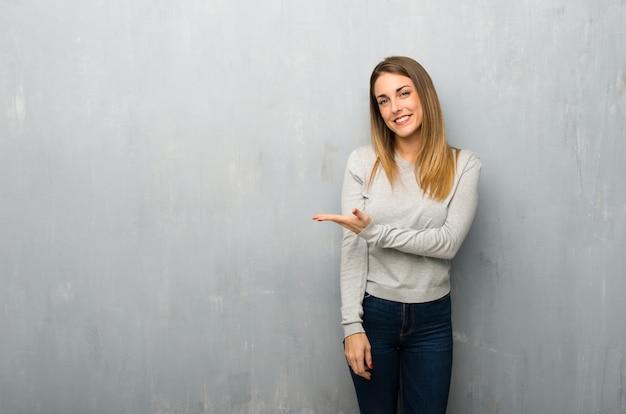 Mujer joven en la pared texturizada que presenta una idea mientras que mira sonriente hacia