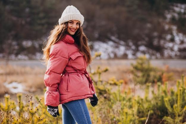 Mujer joven en el parque de invierno feliz