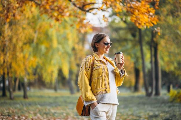 Mujer joven en un parque de otoño tomando café