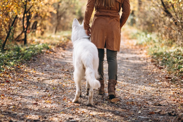 Mujer joven en el parque con su perro blanco