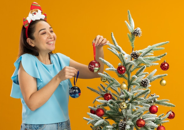 Mujer joven en la parte superior azul con gracioso borde navideño en la cabeza de pie junto a un árbol de navidad sosteniendo bolas de navidad mirando ar árbol sonriendo alegremente sobre fondo naranja