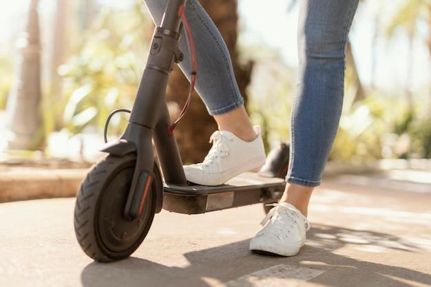 Mujer joven paseos en un scooter eléctrico en la ciudad