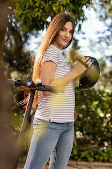 Mujer joven paseos en un scooter eléctrico en un parque