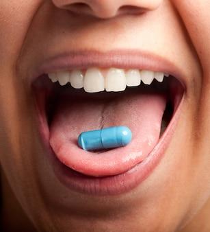 Mujer joven con una pastilla en la lengua