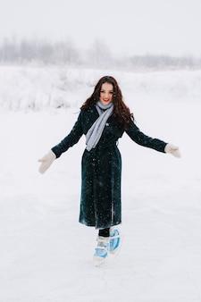 Mujer joven patinaje sobre hielo al aire libre en un estanque en un helado día de invierno
