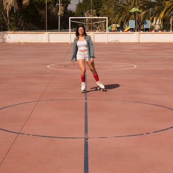 Mujer joven patinando en la cancha de fútbol al aire libre