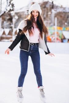 Mujer joven patinando en una pista en un centro de la ciudad