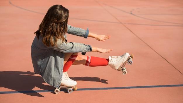 Mujer joven con patines en cuclillas y estirando las piernas y la mano en la cancha