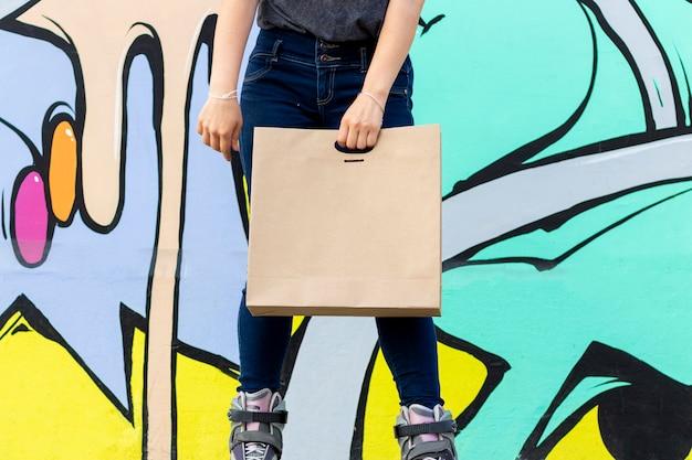 Mujer joven en patines entregando comida en bolsa de papel
