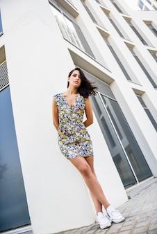 Mujer joven con el peinado ondulado que se coloca al lado del edificio moderno.