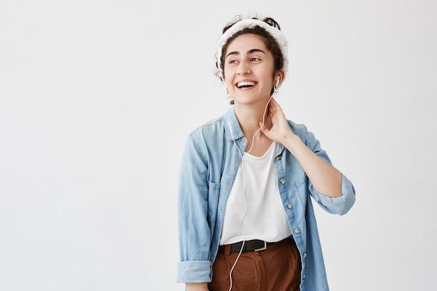 Mujer joven con peinado oscuro y ondulado, viste camisa vaquera, se ve felizmente a un lado, se ríe, tiene buen humor, escucha audiolibros con auriculares, aislados en la pared blanca