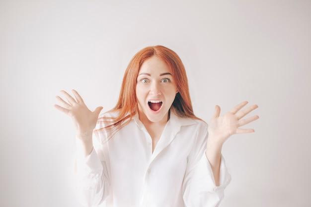 Una mujer joven y pelirroja aislada sobre un fondo blanco con una camiseta blanca tiene una sorpresa, deleite y alegría. ella abrió la boca y gritó a la cámara.