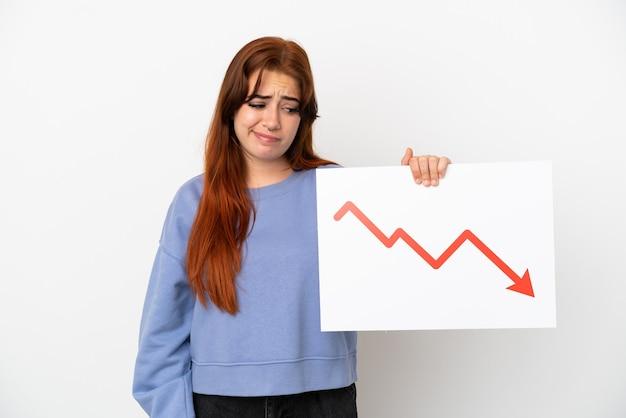 Mujer joven pelirroja aislada sobre fondo blanco con un cartel con un símbolo de flecha de estadísticas decrecientes con expresión triste