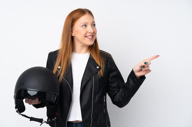 Mujer joven pelirroja con un casco de moto sobre pared blanca aislada apuntando hacia un lado para presentar un producto