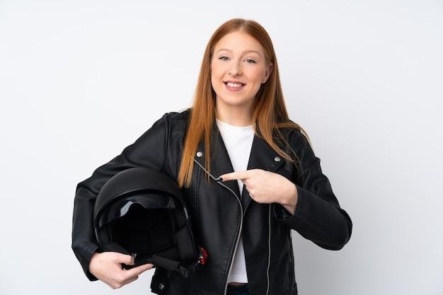 Mujer joven pelirroja con un casco de moto sobre pared blanca aislada y apuntando