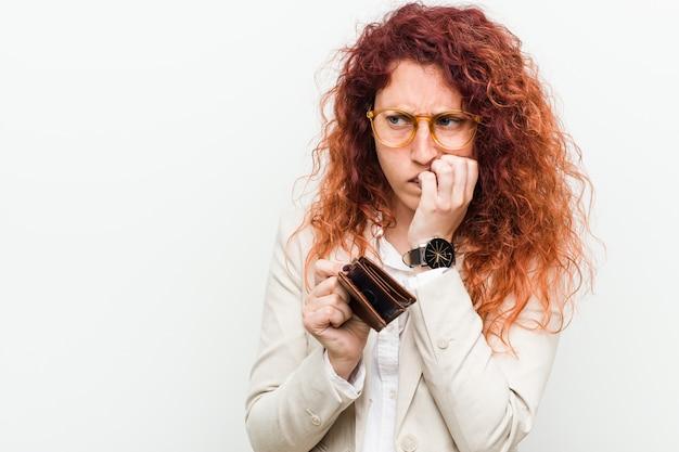 Mujer joven pelirroja caucásica sosteniendo una billetera morderse las uñas, nervioso y muy ansioso.