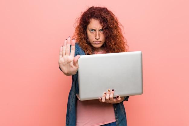 Mujer joven pelirroja caucásica sosteniendo una computadora portátil de pie con la mano extendida que muestra la señal de stop, impidiéndole.