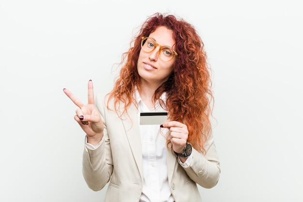 Mujer joven pelirroja caucásica sosteniendo una tarjeta de crédito que muestra el número dos con los dedos.