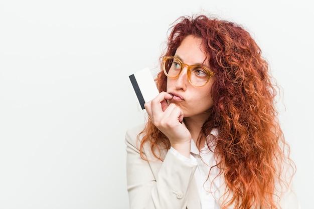 Mujer joven pelirroja caucásica sosteniendo una tarjeta de crédito relajado pensando en algo mirando un espacio de copia.