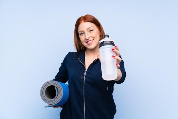 Mujer joven pelirroja deporte sobre azul aislado con botella de agua deportiva y con una estera