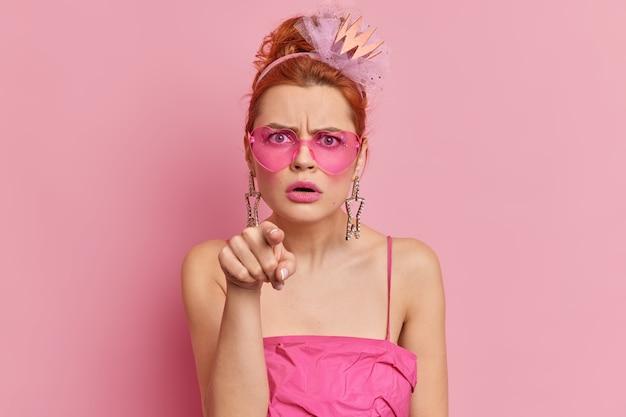 La mujer joven pelirroja enojada usa gafas de sol con estilo y el vestido indica directamente con la expresión de la cara molesta que ve algo impresionante aislado sobre una pared rosa. disparo monocromo. eh, tú