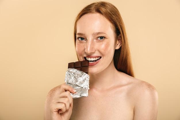 Mujer joven pelirroja feliz comiendo chocolate. mirando la cámara.