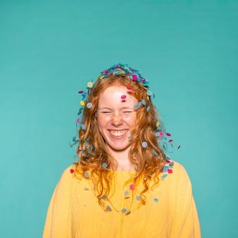 Mujer joven pelirroja de fiesta con confeti en el pelo