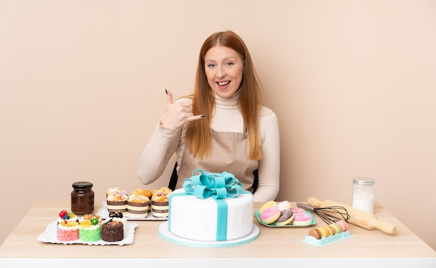 Mujer joven pelirroja con un gran pastel haciendo gesto de teléfono