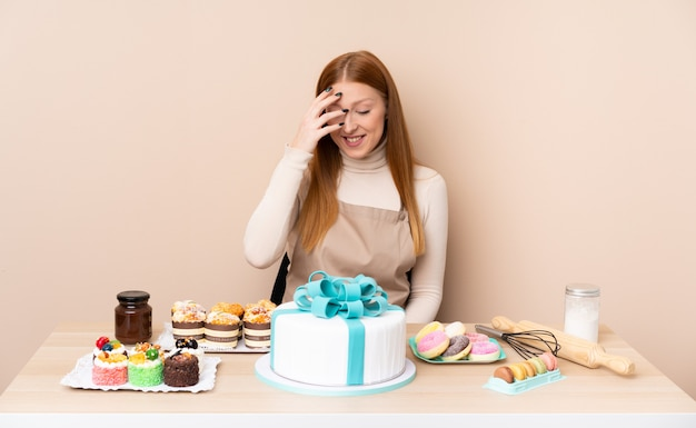 Mujer joven pelirroja con un gran pastel riendo