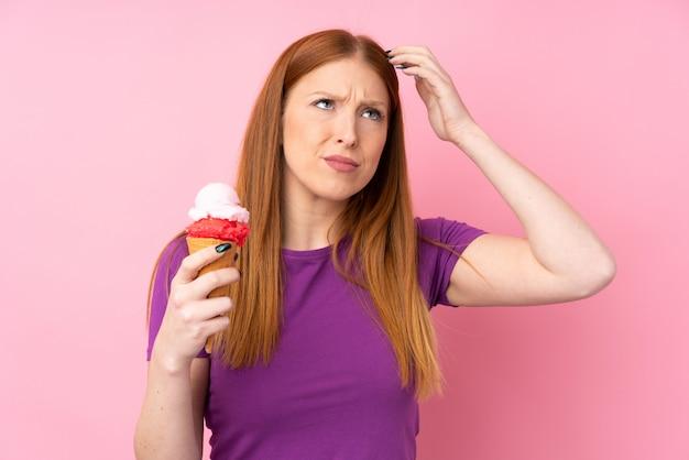 Mujer joven pelirroja con un helado de cucurucho sobre pared rosa aislada con dudas y con expresión de la cara confusa