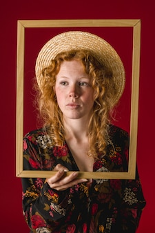 Mujer joven pelirroja con marco de madera