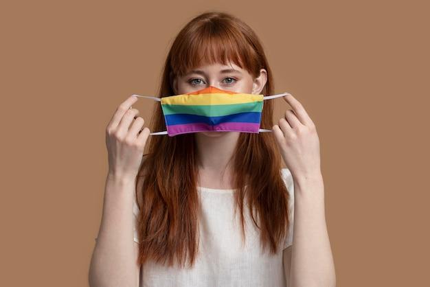 Mujer joven pelirroja con máscara médica arco iris