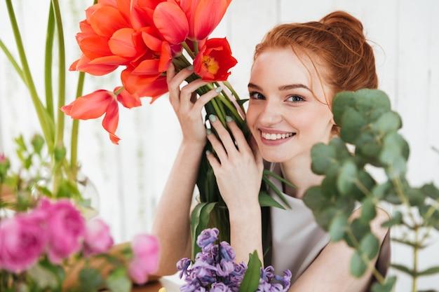 Mujer joven pelirroja mirando hacia arriba y sosteniendo tulipanes rojos