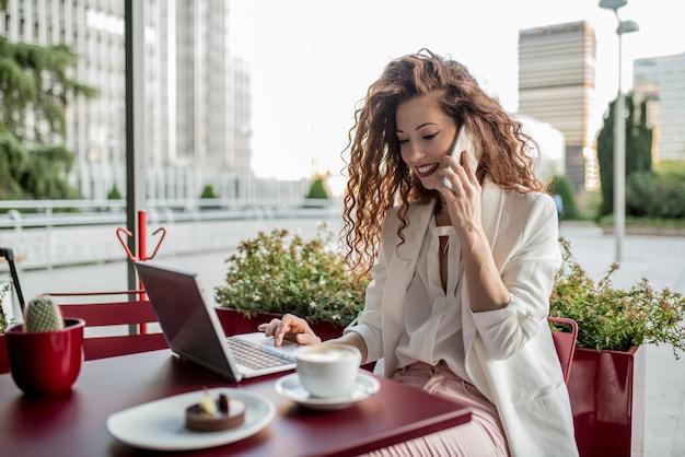 Mujer joven pelirroja de negocios en la computadora y el teléfono móvil