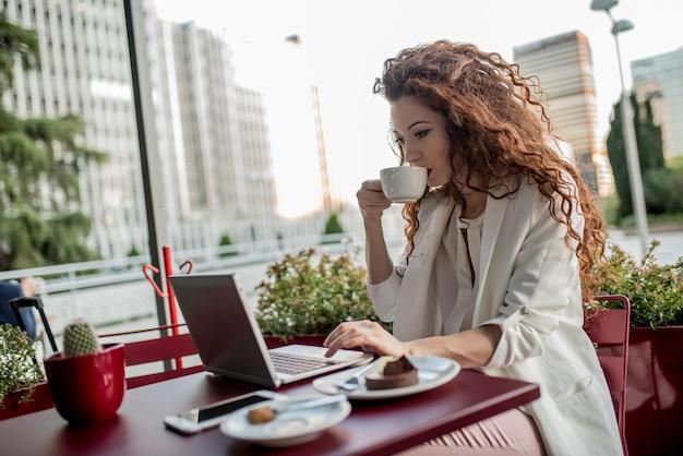 Mujer joven pelirroja de negocios en la computadora y tomando un café